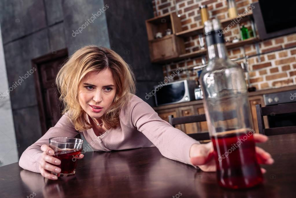 selective focus of drunk woman taking bottle of alcohol while sitting at table at home
