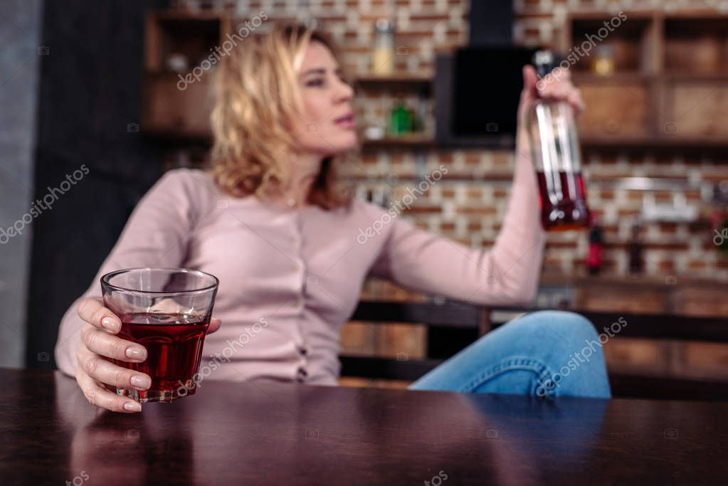 selective focus of woman with bottle of alcohol sitting at table in kitchen
