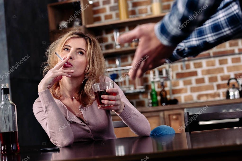 partial view of man arguing with drunk wife that sitting at table in kitchen at home