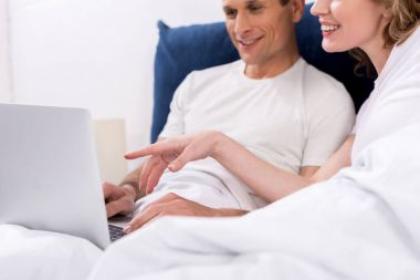 partial view of smiling couple with laptop in bed at home