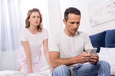 confused wife looking at husband using smartphone while sitting on bed at home