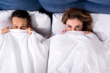 overhead view of wife and husband hiding under blanket while lying in bed at home
