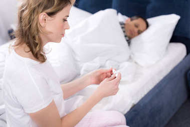 woman looking at thermometer with sick husband in bed near by