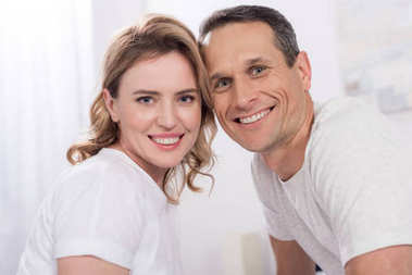 portrait of happy couple looking at camera at home