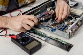 Photo cropped image of hands fixing motherboard of pcwith multimeter