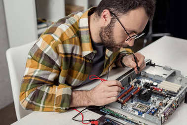 man using multimeter while fixing computer motherboard