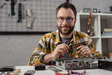 smiling man looking at camera while using multimeter over broken pc