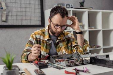 Repairman using multimeter while fixing broken computer and looking down stock vector