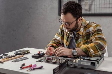repairman using multimeter while fixing computer