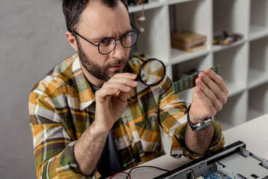 repairman looking on ram and using magnifier