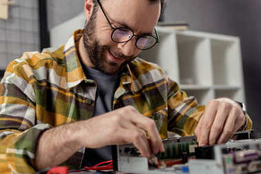 smiling man in glasses fixing computer