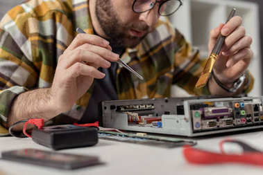 man using multimeter and whisk while fixing computer motherboard