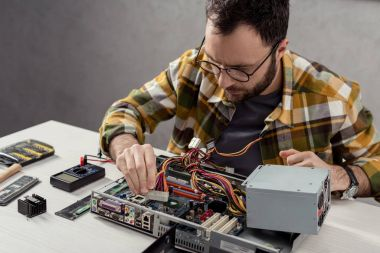 man adjusting details while fixing computer