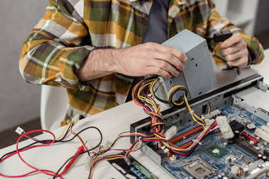 cropped image of repairman fixing computer part