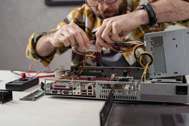 cropped image of man fixing computer part