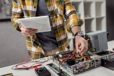 cropped image of man using digital tablet while fixing computer