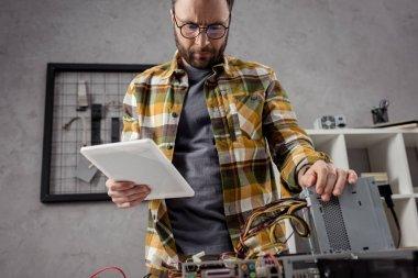Repairman using  digital tablet while fixing broken computer stock vector