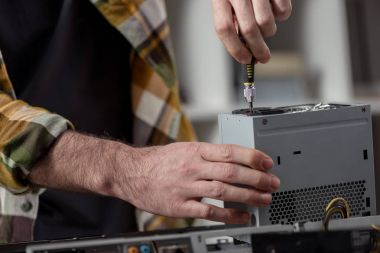 man using screwdriver while fixing computer detail