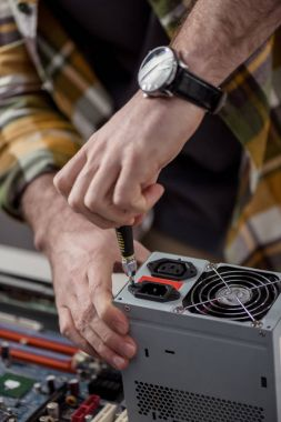 cropped image of repairman fixing computer part  with screwdriver