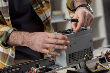 man with screwdriver in hand fixing computer part