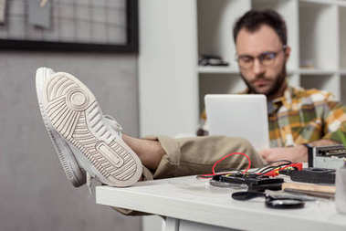 man using digital tablet while sitting on chair with legs on table