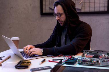 man in hoodie using laptop near broken pc