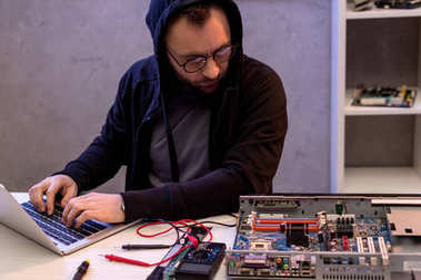 Man in hoodie using laptop while looking on broken pc stock vector