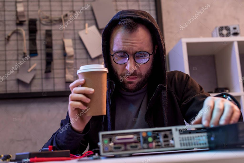 man with coffee in hand looking on broken pc