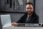Photo smiling man looking at camera while using laptop