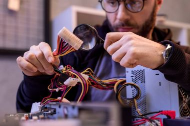 man holding wires in hand and using magnifier while fixing pc