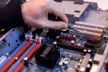 cropped image of hand with tongs adjusting detail on motherboard