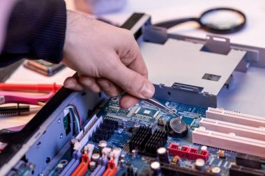 cropped image of repairman fixing motherboard