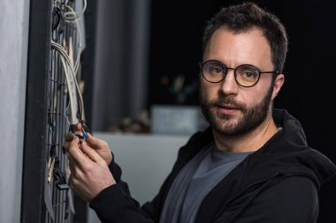 man in glasses  looking at camera while holding wires against wall