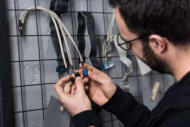 cropped image man holding wires in hands against wall