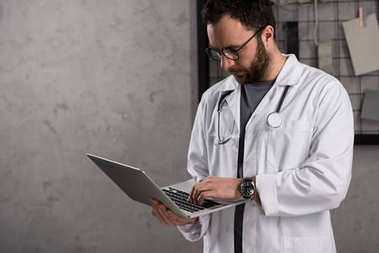 doctot in white coat with stethoscope over his neck using laptop