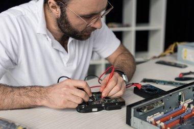 repairman using multimeter while testing hard disk drive