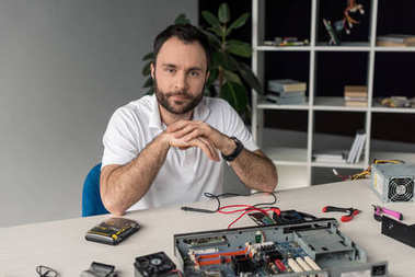 repairman sitting and looking at camera against computer parts on table