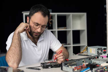 repairman with hand on cheek using multimeter while testing hard disk drive