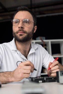 repairman using multimeter while testing hard disk drive  and looking away