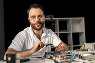 man in glasses looking at camera while he fixing pc