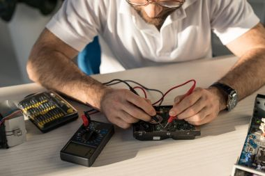 man with multimeter checking computer part on table