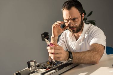 man looking on computer detail in hand