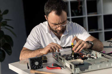 man using screwdriver while fixing computer motherboard