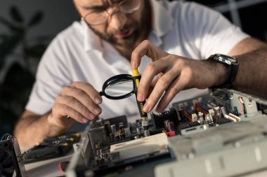 man using magnifier while fixing pc