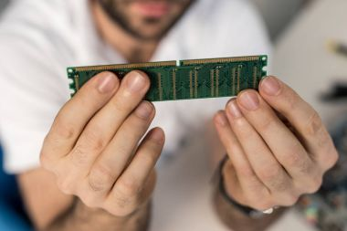 cropped image of man holding ram card in hands