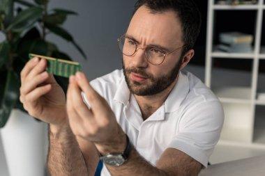 man looking on ram memory in his hands