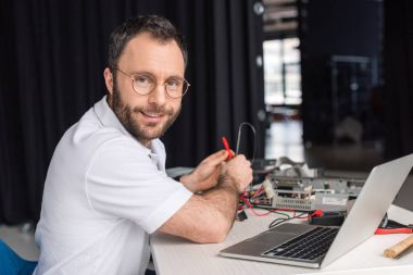 smiling man looking at camera while holding multimeter in hands