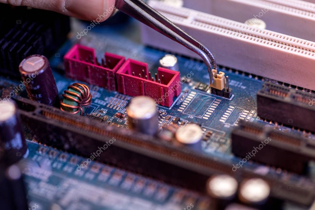 Cropped image of hand with tweezers adjusting detail on motherboard