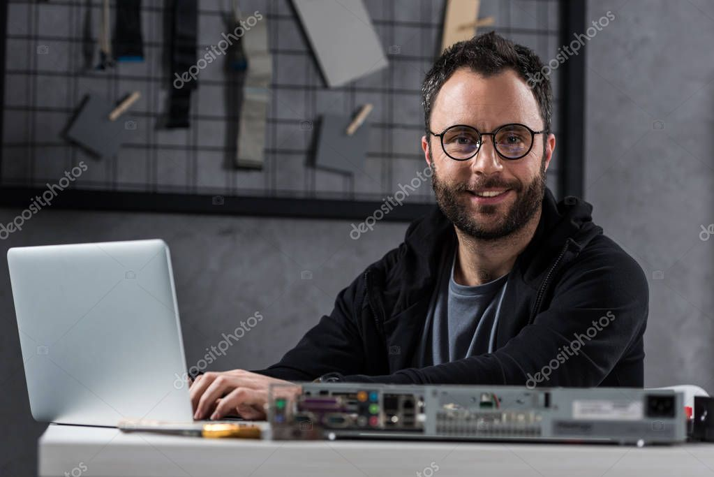 smiling man looking at camera while using laptop