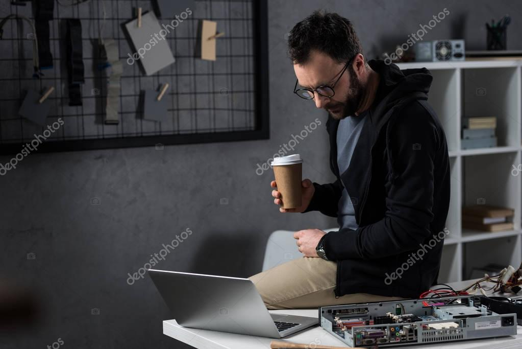man with coffee in hand sitting on table and looking on laptop